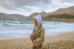 Child on the pebble beach in windy weather royalty free stock photography