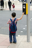 Child at pedestrian crossing. A child boy standing on a pavement or a side walk pushing the button on the traffic  signals for pedestrian crossing, road safety Royalty Free Stock Photo