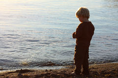 Child Peeing on Beach. A young boy child has his back to the camera and is standing on a beach shoreline, peeing into the water royalty free stock images