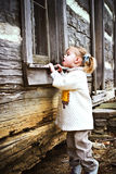 Child peeking. Curious toddler looking inside an old log cabin Royalty Free Stock Photos