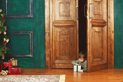 Child peeking from behind the door of the gift Stock Image