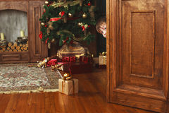 Child peeking from behind the door of the gift Royalty Free Stock Image
