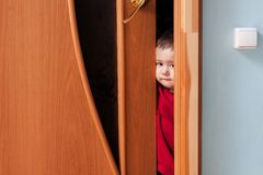 Child peeking from behind the door. A little boy opened the door and looks into the room Stock Photography