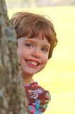 Child peeking from behind a tree. A liitle girl smiles as she peeks out from behind a tree Royalty Free Stock Images