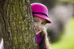 Child peeking behind a tree. Beautiful child peeking behind a tree Stock Photography