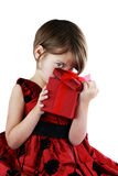 Child Peeking Into Giftbox. A young girl peeking into a gift she has received isolated against a white background with clipping path included Royalty Free Stock Photo