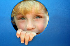 Child Peeking Through Hole at Playground. A cute blonde child is smiling and laughing as he peeks his head through a hole in a playground tunnel on a summer da Stock Image