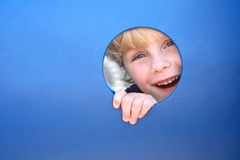 Child Peeking Through Hole at Playground. A cute blonde child is smiling and laughing as he peeks his head through a hole in a playground tunnel on a summer day Stock Photo