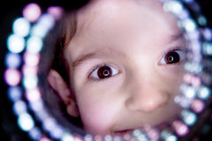 Beautiful eyes. Young child selfie through a circle of light Stock Images