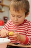 Child peeling potato Royalty Free Stock Photography