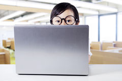 Child peeping from the back of laptop Stock Images