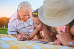 Child with pencil drawing. Caucasian girl outdoors grandparents Stock Photo