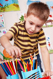 Child  with pencil in play room. Stock Photos