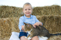 Child with pet. A happy and smiling toddler farm girl dressed in a gingham shirt and blue jean shorts holding a cat while sitting on straw bales Royalty Free Stock Photography