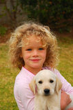 Child and pet. Outdoor portrait of a beautiful little caucasian girl child smiling, sitting and holding her cute Labrador Retriever dog puppy in the backyard Royalty Free Stock Image