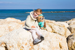Child, pet, summer and vacation concept - Little girl with chihuahua dog on seashore Stock Photos