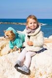 Child, pet, summer and vacation concept - Little girl with chihuahua dog on seashore Stock Photography