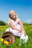Child petting Easter bunny. Child petting the Easter bunny on a spring meadow, eggs in a basket and lots of flowers also to be seen. It is not entirely clear Royalty Free Stock Images
