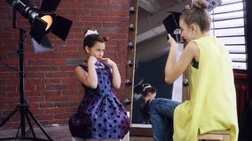 Child photographer holds a photo shoot with a young model. Happy little girls play with the photographer. The model is dressed in Pin up style. A photo session stock footage