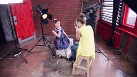 Child photographer holds a photo shoot with a young model. Happy little girls play with the photographer. The model is dressed in Pin up style. A photo session stock video