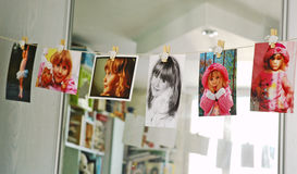 Child photographs. Hanging on a clothesline in room royalty free stock image