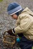 Child picking in basket. Small child putting stones into a basket Stock Photo