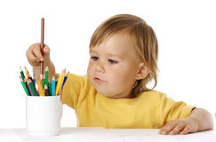 Child picking a crayon from the cup Royalty Free Stock Photography