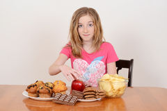 Child picking healthy apple over junk food stock images
