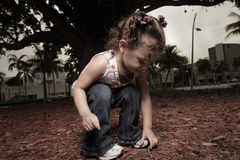 Child picking up something from the ground Royalty Free Stock Photography