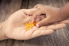 Child picks Cod liver oil omega 3 gel capsules on her mother hand stock image