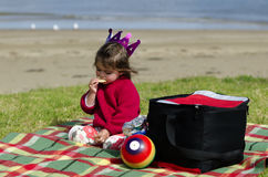 Child on a picnic. Little child eats chips during a picnic on the beach Royalty Free Stock Image