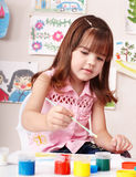 Child with picture and brush in play room. Royalty Free Stock Photography