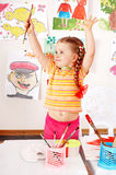 Child with picture and brush in play room. Royalty Free Stock Photo
