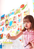 Child with picture and brush in play room. Royalty Free Stock Images