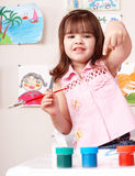 Child with picture and brush in play room. Stock Photography