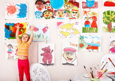 Child with picture and brush in playroom. Royalty Free Stock Photo