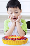 Child with a pie in kitchen Stock Image