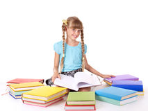 Child with pile of books reading on floor. Royalty Free Stock Images