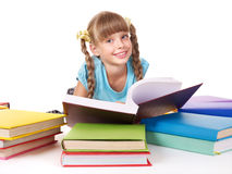 Child with pile of books reading on floor. Stock Photo