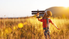 Child pilot aviator with airplane dreams of traveling in summer Royalty Free Stock Photo