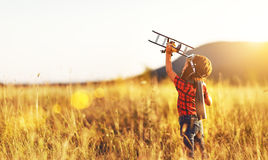 Child pilot aviator with airplane dreams of traveling in summer. In nature at sunset royalty free stock images