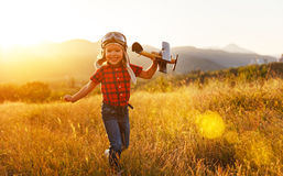 Child pilot aviator with airplane dreams of traveling in summer Stock Image