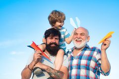 Child pilot aviator with paper airplane dreams of traveling. Fathers day - grandfather, father and son are hugging and royalty free stock photo