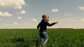 The child in the pilot`s suit runs along the green field, showing his hands on the flight of the aircraft at a slow pace. The boy is running against the sunset stock footage