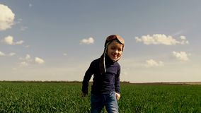 A child in a pilot`s suit runs along the green field, showing his hands the flight of the aircraft at a slow pace. The boy runs to the camera. Slow motion stock footage