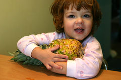 Child and pineapple. Little child cuddling big pineapple Stock Photo