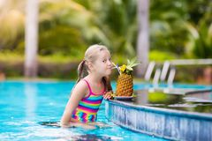 Child with pineapple juice in pool bar stock photo