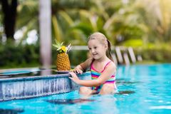 Child with pineapple juice in pool bar stock photos