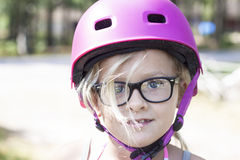 Child with pink bicycle helmet and black glasses royalty free stock photos