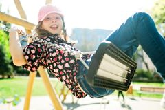 Child in pink cap swinging on Playground - carefree childhood stock images